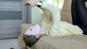Η νέα γυναίκα που κάνει την του προσώπου μάσκα μασκών με να καθαρίσει τη μάσκα, χτυπά στον καναπέ με το smartphone στο σπίτι στοκ εικόνα με δικαίωμα ελεύθερης χρήσης