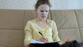 Η νέα γυναίκα που κάνει την του προσώπου μάσκα μασκών με να καθαρίσει τη μάσκα, χτυπά στον καναπέ με το smartphone στο σπίτι στοκ φωτογραφία