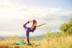 Η νέα γυναίκα που κάνει τη γιόγκα ή η ικανότητα ασκεί το υπαίθριο, τοπίο φύσης στο ηλιοβασίλεμα Στοκ Εικόνες