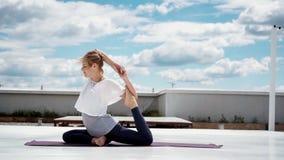 Η νέα γυναίκα που κάνει τη γιόγκα ή pilates η άσκηση ένα με πόδια περιστέρι βασιλιάδων θέτει φιλμ μικρού μήκους