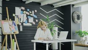 Η νέα γυναίκα που κάνει τη σημείωση για την αυτοκόλλητη ετικέττα και το κολλά σε έναν πίνακα απόθεμα βίντεο