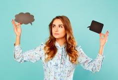 Η νέα γυναίκα που κρατά δύο που η κενή σκέψη βράζει ανωτέρω αυτός διευθύνει Στοκ Φωτογραφία