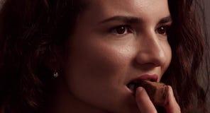 Η νέα γυναίκα που δοκιμάζει μια σοκολάτα και παίρνει μια ευχαρίστηση απόθεμα βίντεο