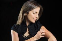 Η νέα γυναίκα που πάσχει από φαγουρίζει μετά από τα δαγκώματα κουνουπιών, σε ένα μαύρο υπόβαθρο στοκ φωτογραφία