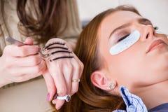 Η νέα γυναίκα που παίρνει eyelash την επέκταση στοκ εικόνες με δικαίωμα ελεύθερης χρήσης