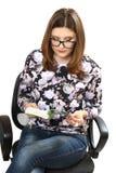 Η νέα γυναίκα που φορά τα γυαλιά διαβάζει το βιβλίο Στοκ Εικόνες