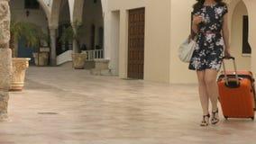 Η νέα γυναίκα που φορά το φόρεμα και το καπέλο φέρνει τις αποσκευές στο ξενοδοχείο, περπατά γύρω από την πόλη απόθεμα βίντεο