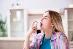 Η νέα γυναίκα που χρησιμοποιεί τον εισπνευστήρα για να αντιμετωπίσει το άσθμα στοκ εικόνες
