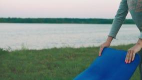 Η νέα γυναίκα προετοιμάζεται να κάνει την πρακτική γιόγκας πρωινού υγιής τρόπος ζωής έννοιας απόθεμα βίντεο
