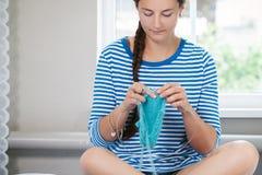 Η νέα γυναίκα πλέκει έναν μάλλινο στοκ φωτογραφίες