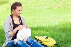 Η νέα γυναίκα πλέκει με το πλέξιμο των βελόνων Στοκ Εικόνες