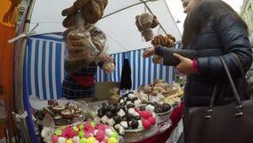 Η νέα γυναίκα πληρώνει τον προμηθευτή για τα ζωηρόχρωμα γλυκά στην αγορά καταστημάτων καραμελών φιλμ μικρού μήκους