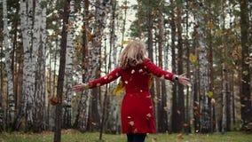 Η νέα γυναίκα ρίχνει επάνω στα πεσμένα κίτρινα φύλλα και κατοχή της διασκέδασης το κορίτσι στο κόκκινο παλτό στο δάσος φθινοπώρου απόθεμα βίντεο