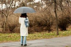 Η νέα γυναίκα σε ένα άσπρο παλτό με μια ομπρέλα περπατά στο πάρκο Στοκ φωτογραφία με δικαίωμα ελεύθερης χρήσης