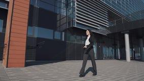 Η νέα γυναίκα σε ένα επιχειρησιακό κοστούμι πηγαίνει ενάντια στο σκηνικό ενός σύγχρονου κτηρίου απόθεμα βίντεο