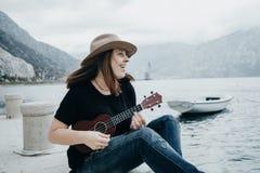 Η νέα γυναίκα σε ένα καπέλο παίζει σε ένα ukulele στο υπόβαθρο ενός β Στοκ Εικόνες