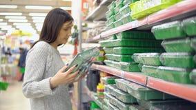 Η νέα γυναίκα σε ένα κατάστημα κήπων επιλέγει τα εμπορευματοκιβώτια για τα σπορόφυτα απόθεμα βίντεο
