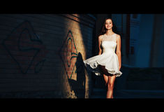 10c6a58e8f83 Η νέα γυναίκα σε ένα κοντό άσπρο φόρεμα περπατά κατά μήκος μιας  εγκαταλειμμένης οδού σε ένα