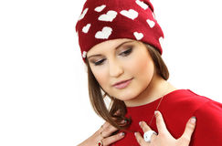 Η νέα γυναίκα σε ένα κόκκινο φόρεμα και μια κόκκινη ΚΑΠ με τις καρδιές στοκ φωτογραφία