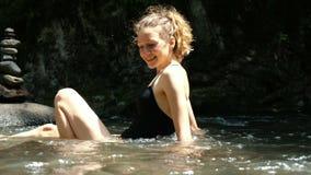 Η νέα γυναίκα σε ένα μαγιό μετρίασε σε έναν κρύο ποταμό βουνών, κραυγάζοντας συναισθηματικά από το κρύο απόθεμα βίντεο