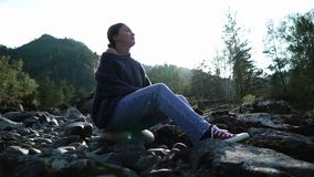Η νέα γυναίκα σε ένα πουλόβερ κάθεται στις πέτρες στο βουνό στην ηλιόλουστη ημέρα σκιαγραφία απόθεμα βίντεο