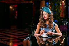 Η νέα γυναίκα σε ένα τυρκουάζ φόρεμα κάθεται σε ένα νυχτερινό κέντρο διασκέδασης και πίνει τον καφέ στοκ εικόνες