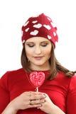 Η νέα γυναίκα σε μια κόκκινη ΚΑΠ με τις καρδιές και με την καραμέλα ζάχαρης αυτός στοκ φωτογραφία με δικαίωμα ελεύθερης χρήσης