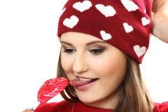 Η νέα γυναίκα σε μια κόκκινη ΚΑΠ με τις καρδιές και με την καραμέλα ζάχαρης αυτός στοκ εικόνες με δικαίωμα ελεύθερης χρήσης