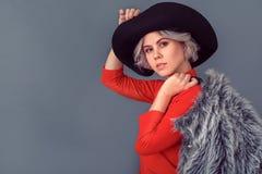 Η νέα γυναίκα σε μια κόκκινη μπλούζα και η γούνα ντύνουν στον γκρίζο πυροβολισμό περιοδικών τοίχων στοκ εικόνες