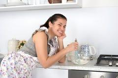 Η νέα γυναίκα σε μια ποδιά παρεμποδίζει μια ζύμη Nimbus στην κουζίνα και χαμογελά στοκ φωτογραφίες