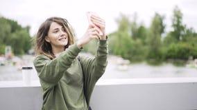 Η νέα γυναίκα σε πράσινο παίρνει ένα selfie σε μια γέφυρα κοντά σε έναν ποταμό φιλμ μικρού μήκους