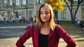 Η νέα γυναίκα, σπουδαστής είναι καιη, διασχίζοντας τα όπλα της στο στήθος στο υπόβαθρο του πανεπιστημίου, υπαίθρια απόθεμα βίντεο