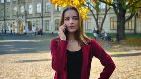 Η νέα γυναίκα σπουδαστής μιλά στο τηλέφωνο και ακούει τις κακές ειδήσεις, που στέκονται έξω από το πανεπιστήμιο Δυσάρεστο τηλεφών απόθεμα βίντεο