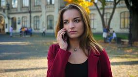 Η νέα γυναίκα σπουδαστής μιλά στο τηλέφωνό της έξω από το πανεπιστήμιο, παίρνει και κοιτάζει στο ρολόι Αναμονή έξω από απόθεμα βίντεο