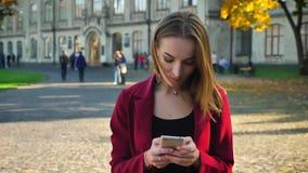 Η νέα γυναίκα σπουδαστής στέκεται το μήνυμα σε ένα τηλέφωνο, παίρνει ενοχλημένη και έπειτα χαμόγελα, έξω από το πανεπιστήμιο σε μ απόθεμα βίντεο