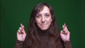 Η νέα γυναίκα σπουδαστής brunette κάνει τη χειρονομία δια:σχίζω-δάχτυλων προσευμένος για την επιτυχία στο πράσινο υπόβαθρο απόθεμα βίντεο