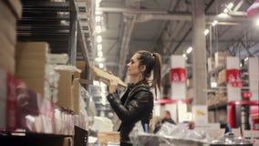 Η νέα γυναίκα στέκεται κοντά στα ράφια με τα αγαθά, ψάχνοντας το απαραίτητο κιβώτιο, το κράτημα σε την παραδίδει μια αποθήκη εμπο απόθεμα βίντεο