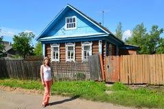 Η νέα γυναίκα στέκεται κοντά στο αγροτικό ξύλινο σπίτι Στοκ φωτογραφία με δικαίωμα ελεύθερης χρήσης