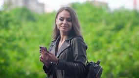 Η νέα γυναίκα στέκεται υπαίθρια στην ηλιόλουστη ημέρα και χρησιμοποιεί το κινητό τηλέφωνό της, σχηματίζει τον αριθμό και κοιτάζει απόθεμα βίντεο