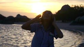 Η νέα γυναίκα στα ακουστικά έχει τους χορούς μουσικής ακούσματος διασκέδασης στην παραλία στο καταπληκτικό ηλιοβασίλεμα σε σε αργ φιλμ μικρού μήκους