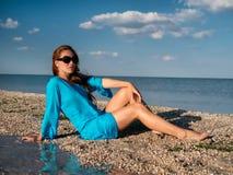 Η νέα γυναίκα στα γυαλιά ηλίου, μπλε tunika κάθεται στην παραλία και εξετάζει τη θάλασσα στο ηλιόλουστο γέλιο γυναικών χαμόγελου  στοκ φωτογραφίες
