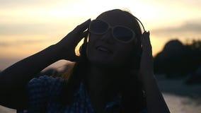 Η νέα γυναίκα στα γυαλιά ηλίου που φορούν τα ακουστικά έχει τη μουσική ακούσματος διασκέδασης στην παραλία στο καταπληκτικό ηλιοβ απόθεμα βίντεο