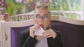 Η νέα γυναίκα στα γυαλιά που κάθεται σε έναν πίνακα σε ένα εστιατόριο σκουπίζει το στόμα της με μια πετσέτα εγγράφου απόθεμα βίντεο