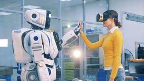 Η νέα γυναίκα στα εικονικά γυαλιά αγγίζει ένα χέρι ενός ανθρώπινος-όπως ρομπότ απόθεμα βίντεο