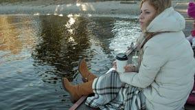 Η νέα γυναίκα, στα θερμά ενδύματα, κάθεται στις όχθεις του ποταμού, στο λιμένα ποταμών, πίνει το τσάι, πικ-νίκ φιλμ μικρού μήκους