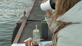 Η νέα γυναίκα, στα θερμά ενδύματα, κάθεται στις όχθεις του ποταμού, στο λιμένα ποταμών, πίνει το τσάι, πικ-νίκ απόθεμα βίντεο