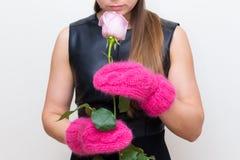 Η νέα γυναίκα στα κόκκινα γάντια κρατά αυξήθηκε στοκ φωτογραφία με δικαίωμα ελεύθερης χρήσης
