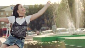 Η νέα γυναίκα στα σορτς τζιν παίζει coquettishly στο νερό σε μια πηγή πόλεων κάνοντας τους παφλασμούς φιλμ μικρού μήκους