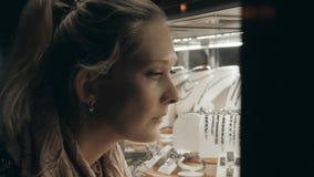 Η νέα γυναίκα στα υφάσματα φθινοπώρου εξετάζει την προθήκη με το κόσμημα στην οδό βραδιού απόθεμα βίντεο