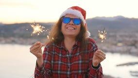 Η νέα γυναίκα στα Χριστούγεννα ή το νέο έτος ντύνουν και διακοπές εκμετάλλευσης καπέλων οι χειμερινές sparkler και η πυρκαγιά της απόθεμα βίντεο